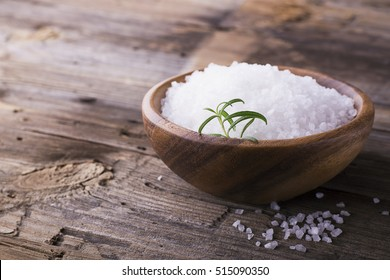Large White sea salt in a natural wooden bowl with a sprig of fresh rosemary on a simple wooden background. Selective focus. room for text