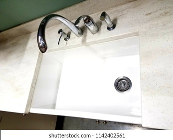 A large white sink with stainless steel faucet