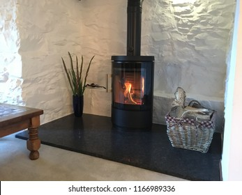 Large white stone inglenook fireplace in a country cottage with a roaring log burner and basket full of logs for fuelling the fire symbolising Winter, log burners and alternative to central heating
