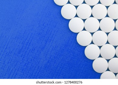 Large white tablets on a blue textured background with space for copy