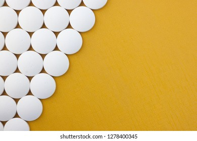 Large white tablets on a yellow textured background with space for copy