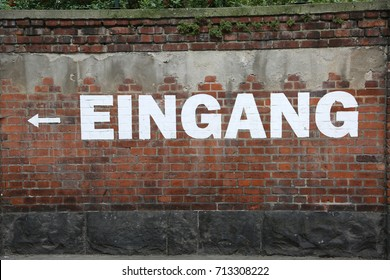 large white text EINGANG on the brick wall which means EXIT in german