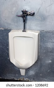 A large white urinal in the mens restroom