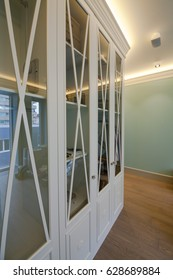 Large white wooden wardrobe with glass doors