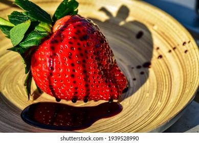 large whole strawberry drizzled with dark balsamic vinegar