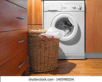 Large Wicker Laundry Basket, Open Lid Near the Washing Machine with Laundry. House Interior Laundry Room. Wood Interior Design.