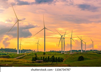 The large wind turbine in the background light in the evening to create natural energy from the wind.