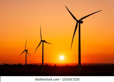 Large wind turbines with blades in field on sky background with bright orange sunset. Silhouettes of windmills, big orange sun disk in summer. Alternative energy sources. Ecological energy