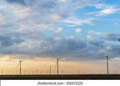Large wind turbines sit before clouds at sunset