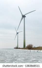 Large windmills in a cloudy sky on a dyke of the frozen Gouwsea near the village of Uitdam in the Netherlands. Generating environmentally friendly electricity. In the winter of early 2018.
