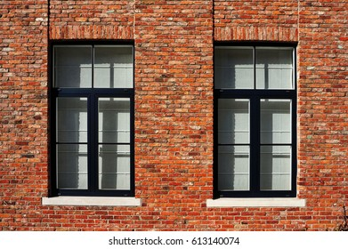 Large window with blue frames on a wall of red bricks