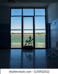 Large window from floor to ceiling to green farmland. Interior view