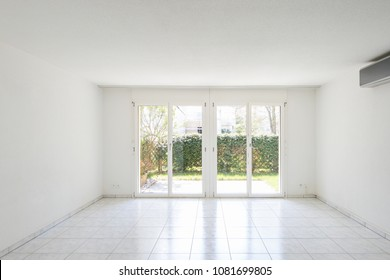 Large windows overlooking the garden in a completely empty room. Nobody inside