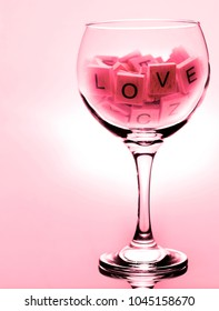 An large wine glass with the words love in scrabble letters, with red color cast