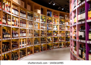 Large wine racks. Many different alcoholic beverages. Luxury enoteca. Photo in blurry.