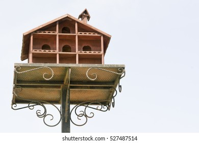 Large wooden birdhouse on a metal pole against the sky