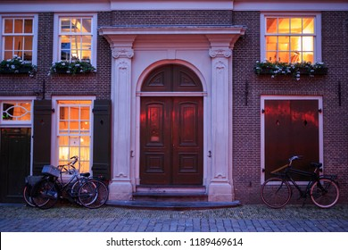 Large wooden door on old brick building with interior lights on