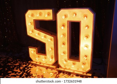 Large wooden figures for the anniversary of 50 years with luminous bulbs inside stand on the floor in a restaurant. Decor for celebration of the anniversary a man. Celebrating an adult guy's birthday