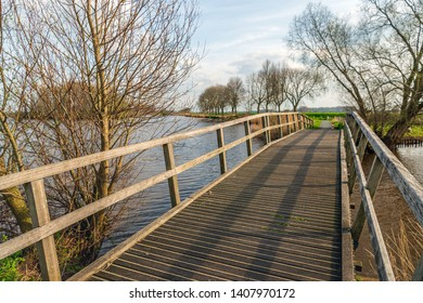 Large wooden footbridge over the water of a lake in the Netherlands. The photo was taken in springtime near the village of Hooge Zwaluwe, Drimmelen, North Brabant.