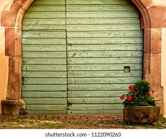 Large wooden green door with stone arch and planter