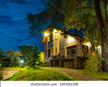 Large wooden house. A stone path in the cottage. A path leads to a wooden house. Lighted two-story cottage at night. Private house in the forest. Holiday cottage in the country. Summer vacation