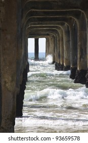 large wooden pier with waves crashing through and under it