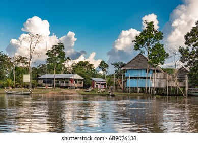 Large wooden shacks with  boats along the Amazon rive with bright blue sky and large white clouds