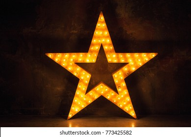 Large wooden star with a large amount of lights in front of dark concrete background.