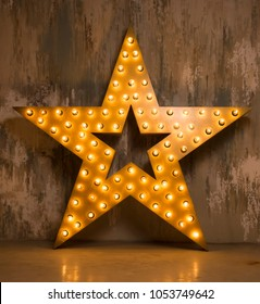 Large wooden star with a large number of lights are lit. Beautiful decor, design. Loft style Studio. Dark concrete background. Christmas, holiday, honorary star. Five stars 5 stars