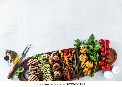 a large wooden tray on a white stone table with a Summer snack, colorful Barbecue Vegetables, cherry tomatoes and greens. summer delicious healthy food for a big company of people or friends