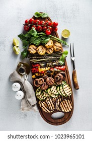 a large wooden tray with a Summer snack, colorful Barbecue Vegetables, cherry tomatoes and greens. summer delicious healthy food for a big company of people or friends