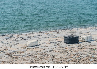 Large worn tractor tire laying on man made concrete ocean causeway embankment with ocean water in background.