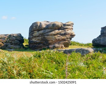 Large worn and weathered gritstone outcrop known as Defiance on Birchen Edge in Derbyshire.