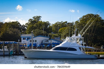 A large yacht sits moored at a small coastal town.