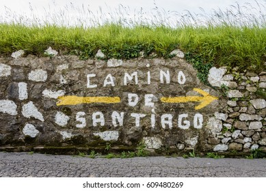 Large yellow arrow and inscription Camino de Santiago on wall along the way of the Way of St. James in Spain