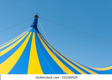 large yellow and blue circus big top canvas against a clear blue sky