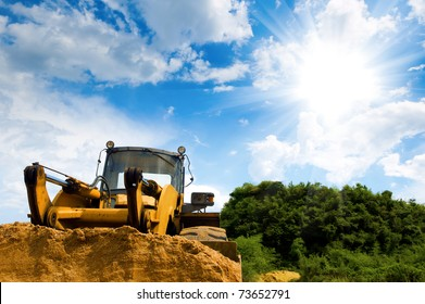 A large yellow bulldozer at a construction site low angle view