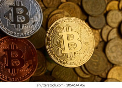 large yellow coin bitcoin on the background of small coins