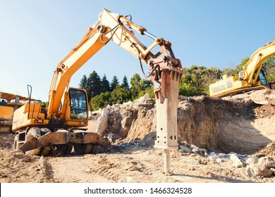 A large yellow construction equipment is digging a pit for the base of a residential complex with an industrial jackhammer. Construction of a large residential building. Initial construction phase
