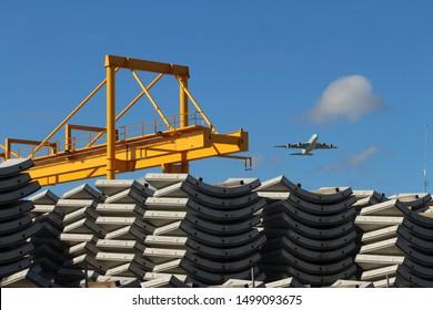 Large yellow crane and tunnel concrete precast segments with plane in the blue sky background. Precast tunnel plant.