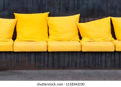 Large yellow cushions in the rest area with a coarse metal base