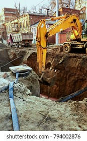 A large yellow excavator in the city digs a pit with a bucket