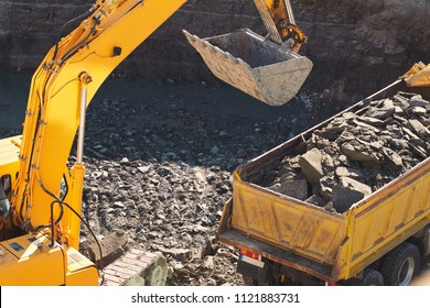 A large yellow excavator digs a foundation pit for the construction of a large residential complex. The bucket heats the ground. Building massive machinery. The initial stage of the new construction