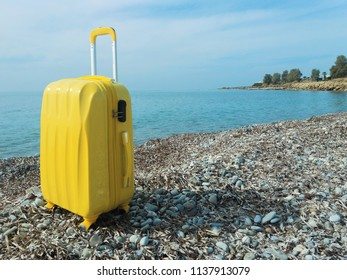 Large Yellow Polycarbonate Suitcase on the beach