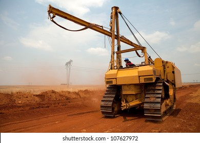 Large yellow side boom pipe layer industrial machine on orange dusty sandy outdoor construction site