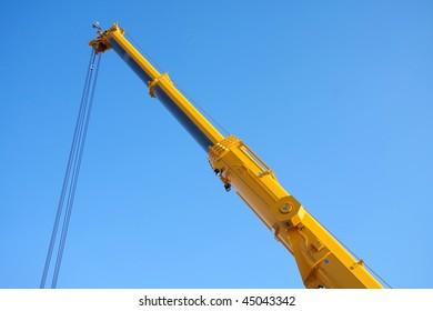 Large yellow telescopic crane, isolated on blue sky