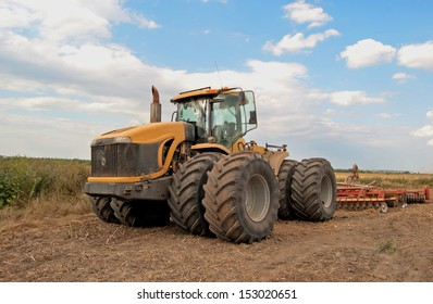 a large yellow tractor processes the field