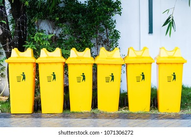 Large yellow trash bin placed 6 side by side.