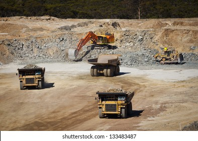 Large yellow trucks used in modern mine Western Australia. Bulldozer moves rock towards digger which fills trucks which transport ore from the open cast mine.