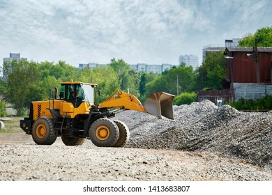 Large yellow wheel loader collects gravel in pile for further loading and transportation. Front wheel loader designed to handle corrosive environments, massive amounts of snow, salt, sand or gravel